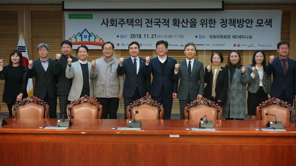 지난 21일 서울 여의도 국회의원회관 제2세미나실에서 '사회주택의 전국적 확산을 위한 정책방안 모색'을 주제로 '2018 사회주택포럼'이 열렸다. 주요 참석자들이 한자리에 모여 주먹을 불끈 쥐고 있다.