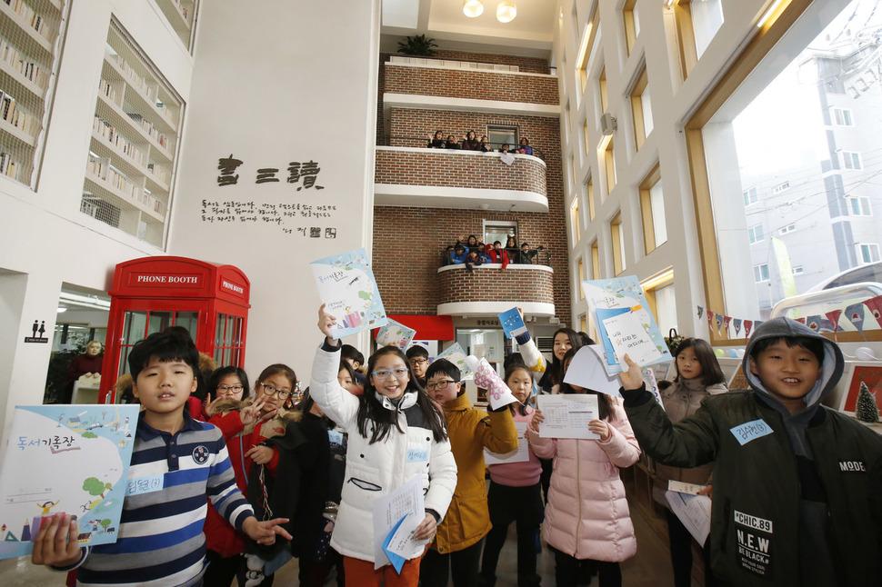 서울 은평구 구립 구산동도서관마을을 찾은 청소년들이 큰 골목길(광장)에서 독서기록장을 들어보이며 활짝 웃고 있다. 이정아 기자 leej@hani.co.kr