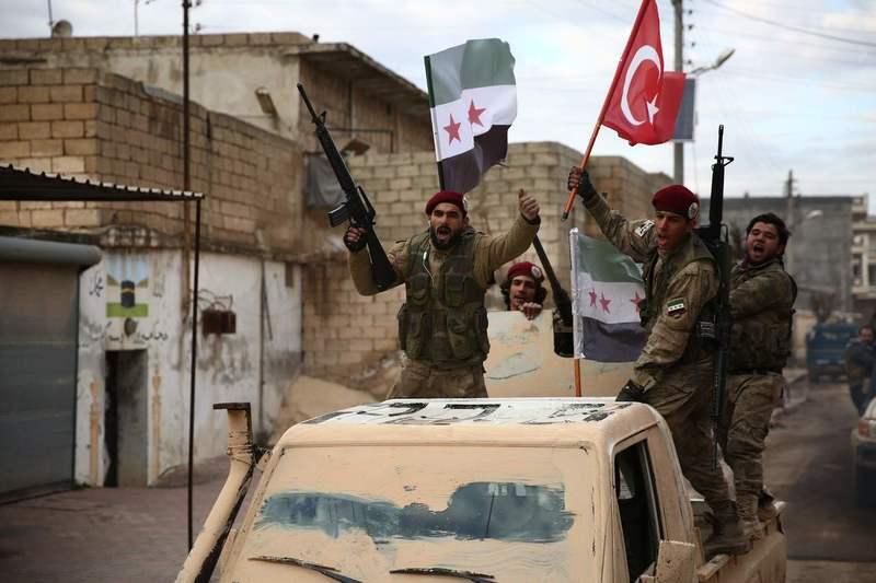 29일 터키의 지원을 받는 시리아 반정부군인 자유시리아군(FSA) 병사들이 시리아 북부 알레포에서 자신들의 깃발과 터키 국기를 흔들며 지나가고 있다. 알레포/AFP 연합뉴스
