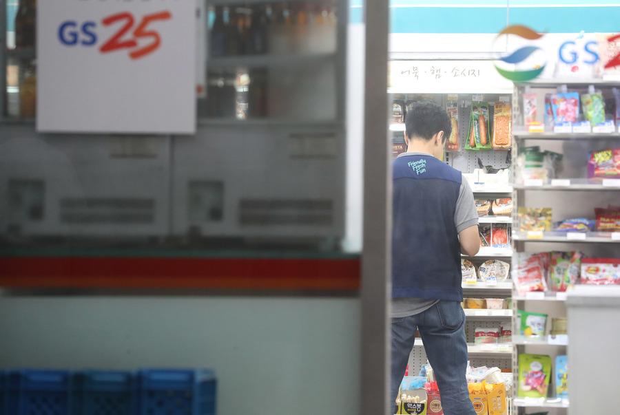 지난해 12월19일 오후 서울 시내 편의점에서 근무하는 노동자들이 손님들을 응대하며 계산하다가 잠시 손님이 없을 때 편의점 진열대를 살피며 수량 등을 체크하고 있다. 신소영 기자 viator@hani.co.kr