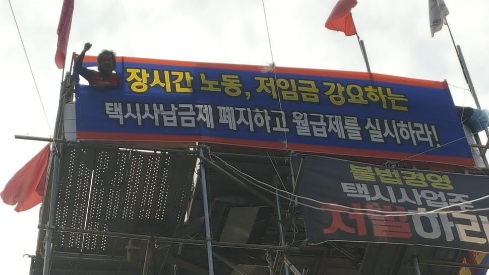 지난 11일 고공농성장에서 손을 들고 있는 김재주 택시지부 전북지회장의 모습. 박임근 기자