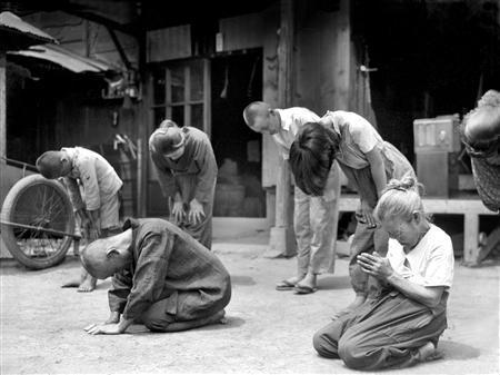 1945년 8월15일 정오 히로히토 일왕이 연합군에게 무조건 항복 선언을 발표한 이른바 '옥음방송'을 듣고 있는 일본인들의 모습. 사진 <점령과 개혁>(아메미야 쇼이치 지음, 유지아 옮김)