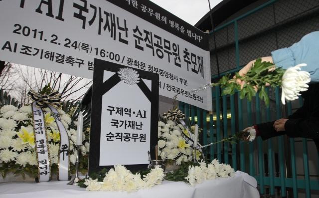 2011년 구제역으로 인해 공무원 6명이 숨졌다. 그해 2월 전국 공무원노동조합이 정부서울청사 후문에서 연 순직 공무원 추모제에서 참석자들이 헌화하고 있다. 이종찬 선임기자 rhee@hani.co.kr