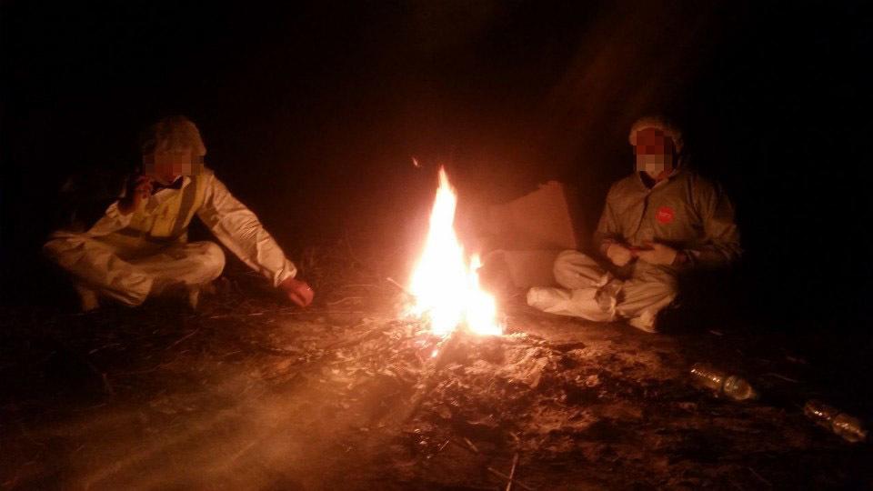 2016년 12월 경기도의 한 축산직 공무원이 산란계 농장에서 살처분 작업을 하던 중 방역복을 입고 불을 쬐며 쉬고 있다. 살처분 노동자 제공