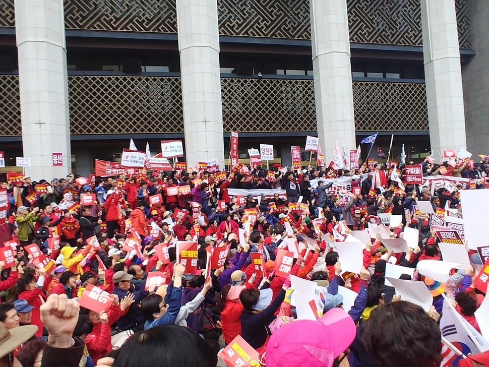 20일 오후 서울 종로구 세종문화회관 앞에서 열린 자유한국당 '문재인 정부 규탄 집회'에 붉은 옷을 입은 당원과 시민들이 앉아있다.