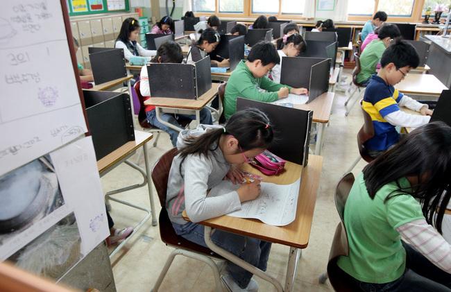 지난해 국가 수준의 학업 성취도 결과에서 중·고등학교 학생들의 기초학력 미달 비율이 늘면서 기초학력 논란이 벌어지고 있다. 사진은 과거 일제고사 형태로 성취도 평가를 할 때 초등학생들이 시험을 보고 있는 모습이다. 일제고사를 보면 학교간·지역간 서열화 분위기가 조장되면서 부작용이 발생할 수 있다. 연합뉴스