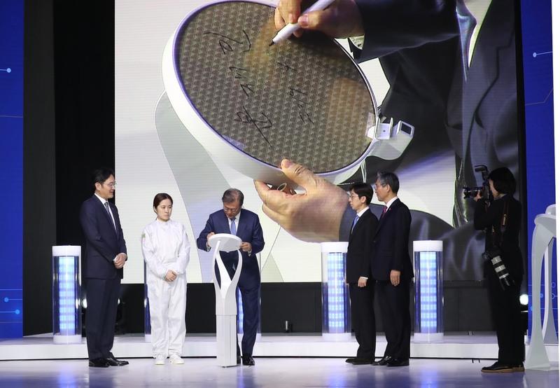 문재인 대통령이 지난달 30일 오후 시스템 반도체 비전 선포식이 열린 삼성전자 화성캠퍼스 부품연구동(DSR)에서 세계최초 극자외선(EUV)공정 7나노로 출하된 웨이퍼·칩에 서명을 하고 있다. 화성/청와대사진기자단