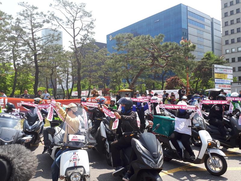 노동절인 5월 1일 국회의사당 맞은편 광장에서 열린 라이더 유니언 출범식에서 조합원들이 '안전하게 일하고 싶다'는 등의 구호가 적힌 띠를 들어 보이고 있다.