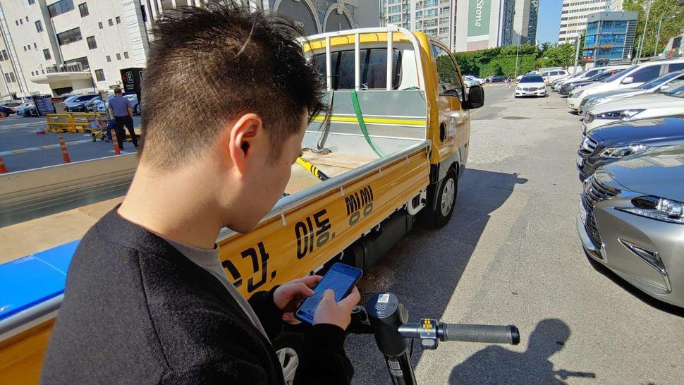 지난 21일 서울 강남의 한 상가건물 앞에서 전동킥보드 공유서비스 '씽씽' 관계자가 휴대전화로 전동킥보드의 위치를 찾고 있다. 박태우 기자