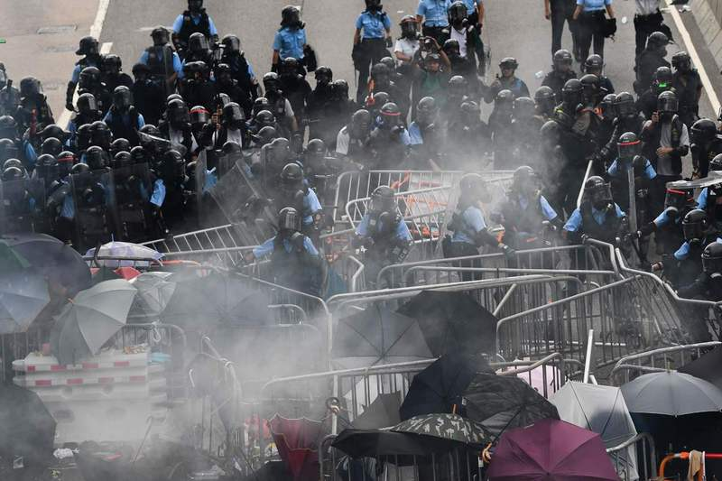 지난 12일 홍콩 정부청사 건물 주변에서 경찰과 범죄인 인도 개정법안에 반대하는 시위대가 충돌하고 있다. 홍콩/AFP 연합뉴스