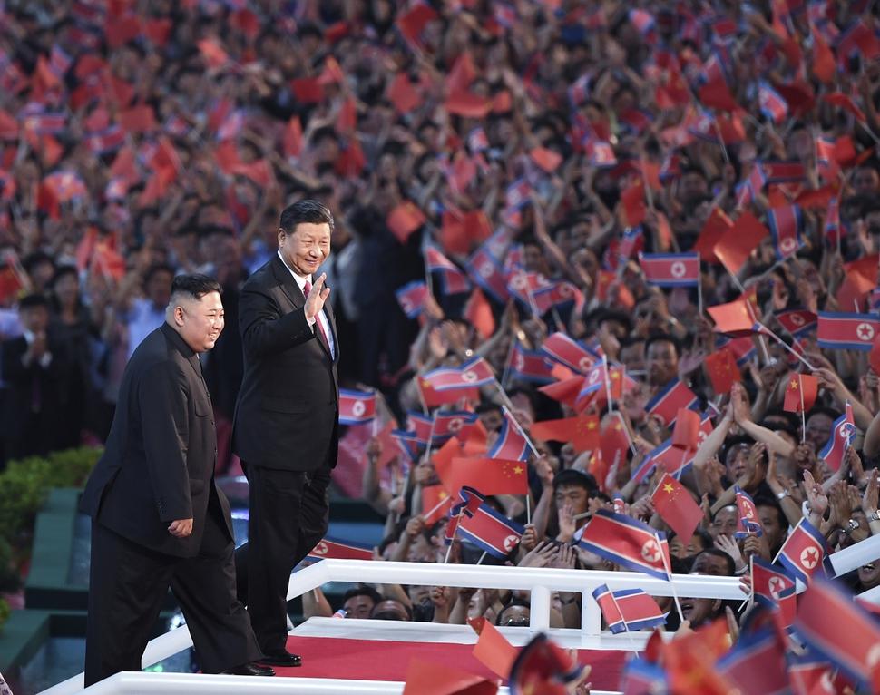 북한을 국빈 방문한 시진핑 중국 국�주석(오른쪽)이 20일 집단 체조를 �람하기 위해 찾� 평양 능라도 5.1경기장(메이데이 스�디�)에 �정� 북한 국무위원장과 함께 들어서며 손들어 인사하고 있다. 평양/신화 연합뉴스