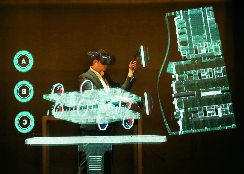 디지털기술은 재난을 효과적으로 극복하도록 도울 수 있다. 지난해 11월 서울 강남구 코엑스에서 열린 '2018 스마트국토엑스포'에서 시민이 3차원 공간정보 홀로그램 컨트롤 타워 체험을 하고 있다.  연합뉴스