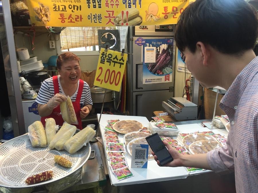 경기도 시흥시 신천동에 있는 삼미시장에서 손님이 지역화폐인 모바일 시루로 옥수수를 사고 있다. 시흥시 제공