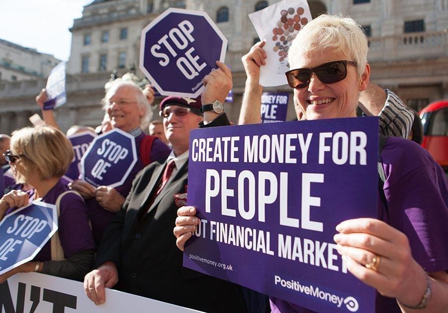 영국의 '주권화폐' 운동단체인 '포지티브머니' 회원들이 2016년 8월 영국은행 앞에서 현행 양적완화 정책에 반대하는 시위를 벌이고 있다. 이들은 민간 은행으로부터 화폐 생산 권력을 빼앗아 국가한테 되돌려주어야 한다는 주장을 폈다. 위키미디어 코먼스