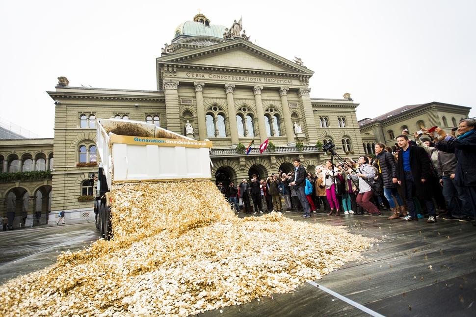2013년 10월 스위스의 기본소득 활동단체 '기본소득세대'가 2013년 10월 스위스 베른의 연방광장 앞에 기본소득 국민투표 청원자가 12만5천명을 넘은 것을 기념해 5센트짜리 동전 800만개(1인당 하나)를 쌓아놓고 환호를 지르고 있다. 2016년 치러진 기본소득 국민투표는 부결됐다. 위키미디어 코먼스