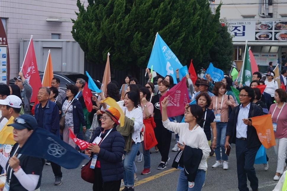 지속가능발전대회에 참가한 참석자들과 시민들이 지속가능발전목표 17개 분야가 적힌 깃발을 들고 거제시내를 걸으며 행진하는 모습.