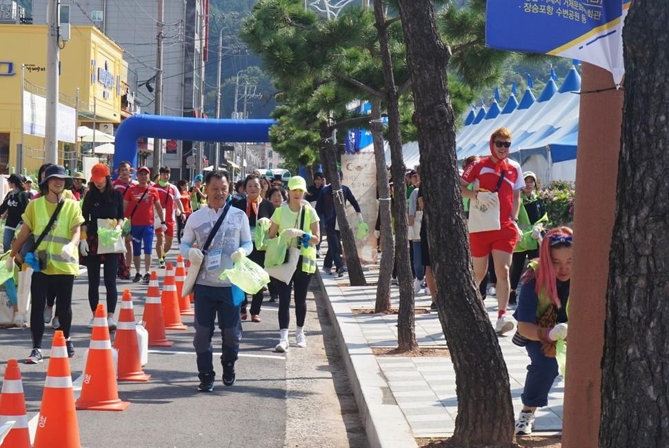 지속가능발전대회에 맞춰 쓰레기 수거와 달리기를 결합한 플로깅 행사가 열려 시민들이 장승포항 수변공원 주변을 뛰며 쓰레기를 줍고 있다.