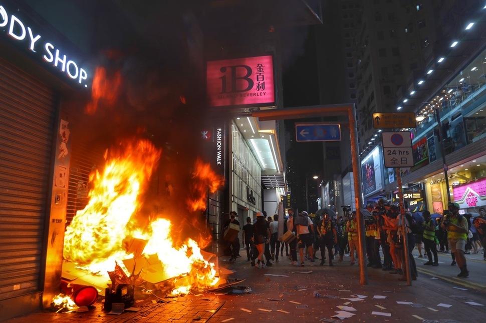 4일 밤 홍콩 도심 거리에서 반정부 시위대가 중국계 점포로 추정되는 한 상점 앞에 불을 지르고 있다. 홍콩/신화 연합뉴스