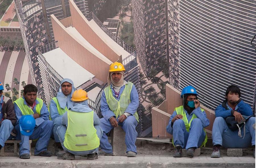 카타르 수도 도하의 한 대형빌딩 건설 현장의 대형 조감도 앞에서 동남아시아 출신 이주노동자들이 앉아 쉬고 있다. 위키피디아