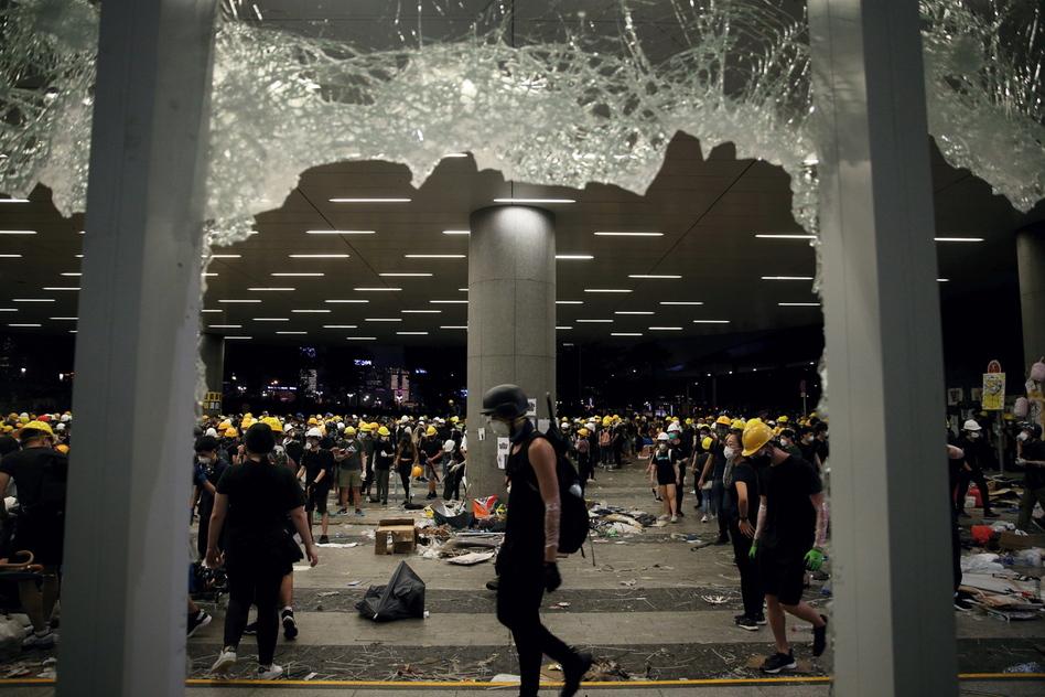 """마스크를 쓴 시위대가 홍콩 의회인 입법회에 지난 7월1일 진입했다. 송환법 철회를 요구하며 홍콩 역사상 처음 의회를 점거한 사건이었다. 이날 경찰의 무력 해산이 임박하자 누군가 마스크를 벗고 """"여기를 지키자""""고 호소했다. 홍콩/EPA 연합뉴스"""