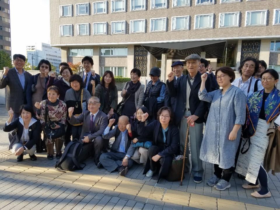 10일 오후 일본 홋카이도 삿포로시 삿포로고등재판소 앞에서 우에무라 다카시(앞줄 왼쪽 셋째) 전  기자와 우에무라 전 기자를 지지하는 한국과 일본 시민들이 손을 들어 보이고 있다.