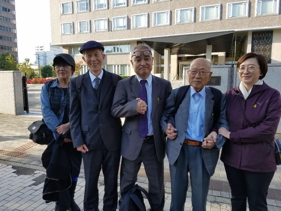 10일 오후 일본 홋카이도 삿포로시 삿포로고등재판소 앞에서 우에무라 다카시(가운데) 전  기자와 우에무라 전 기자를 응원하기 위해 한국에서 온 이들이 손을 잡고 있다.