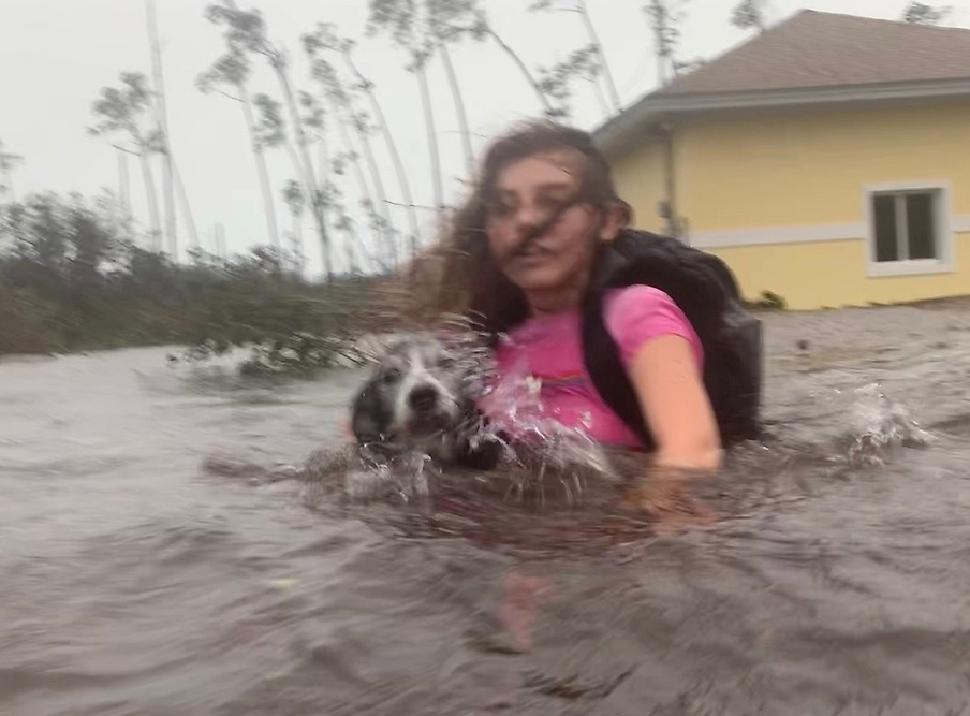 기후변화에 따라 날로 그 규모와 강도가 커지고 있는 풍수해는 도시를 어떻게 설계하고, 운영해 갈 지 고민하게 한다. 사진은 지난 9월 허리케인 도리안이 엄습했을 때 카리브해의 섬나라 바하마의 프리포트에서 한 소녀가 강아지와 함께 구조되는 모습.  AP/ 연합